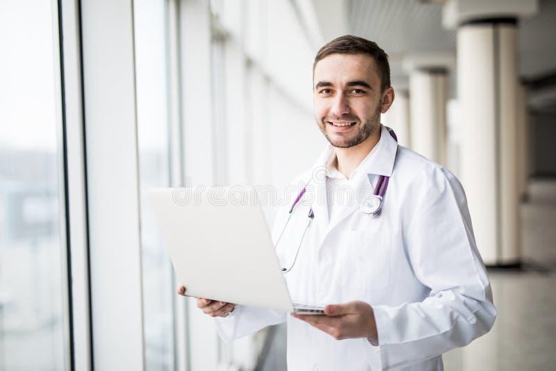 使用膝上型计算机的可爱的年轻医护人员 免版税库存图片