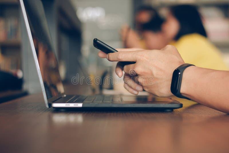 使用膝上型计算机的商人和键入在流动智能手机,有技术概念的商人 手人工作的关闭 库存图片