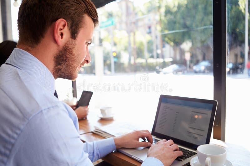 使用膝上型计算机的商人在咖啡店 库存照片