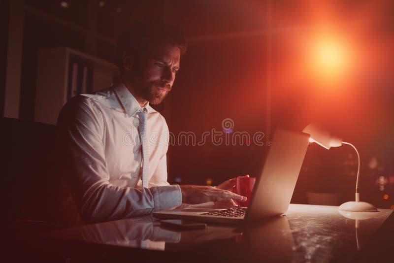 使用膝上型计算机的商人在晚上 库存图片