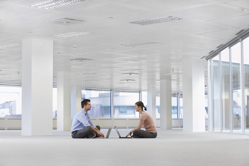 使用膝上型计算机的商人在空的办公室空间 库存图片