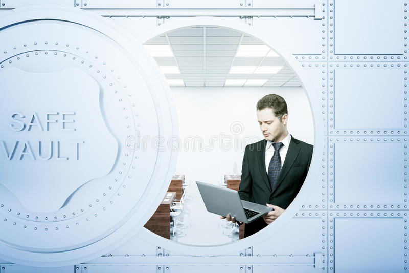 使用膝上型计算机的商人在银行地下室里面 库存图片