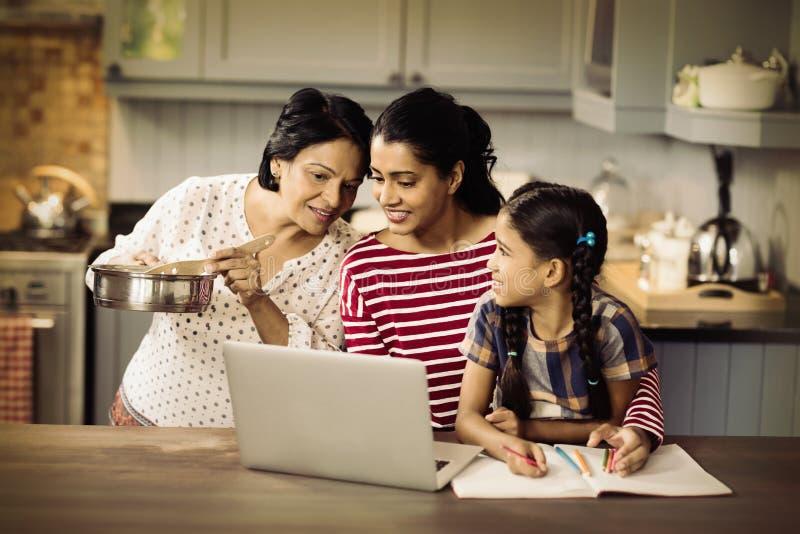 使用膝上型计算机的多代的家庭在厨房里 免版税库存照片