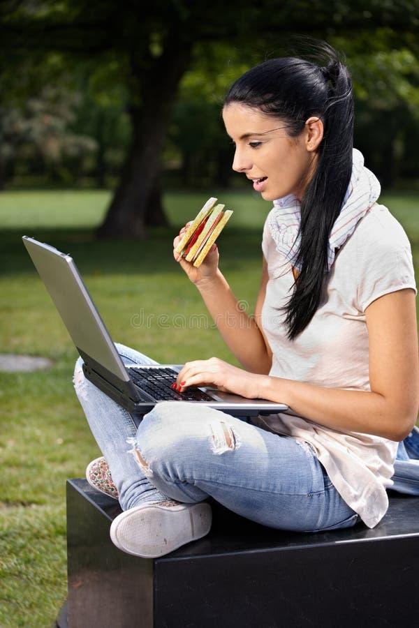 使用膝上型计算机的大学生在吃的公园午餐 免版税库存照片