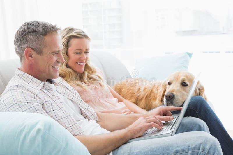 使用膝上型计算机的夫妇和与他们的狗的消费时间 库存图片