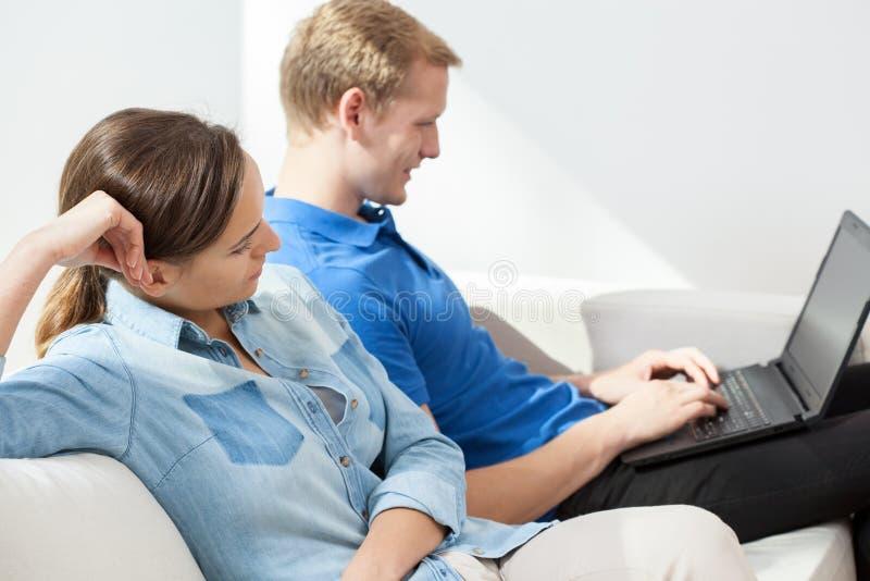 使用膝上型计算机的夫妇在客厅 图库摄影