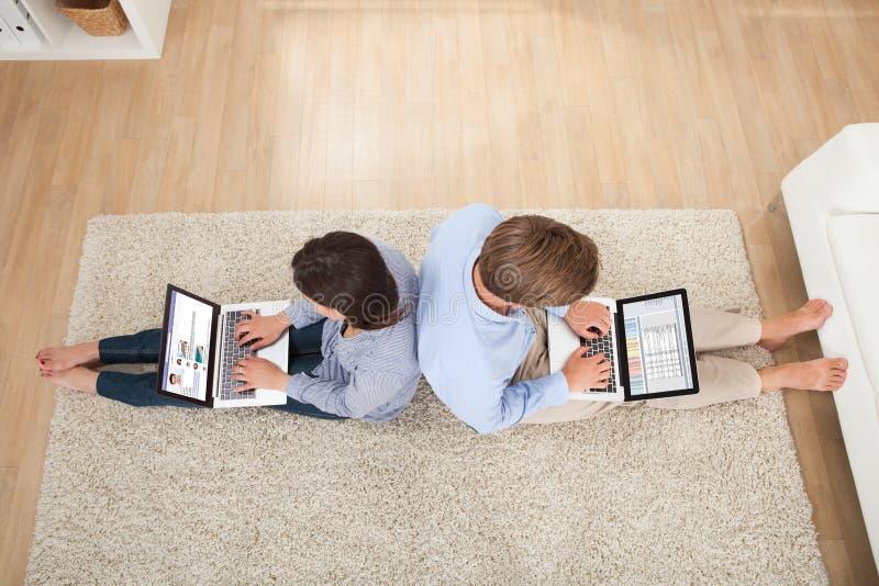使用膝上型计算机的夫妇在客厅 库存照片