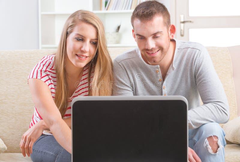 使用膝上型计算机的夫妇在家 免版税库存图片
