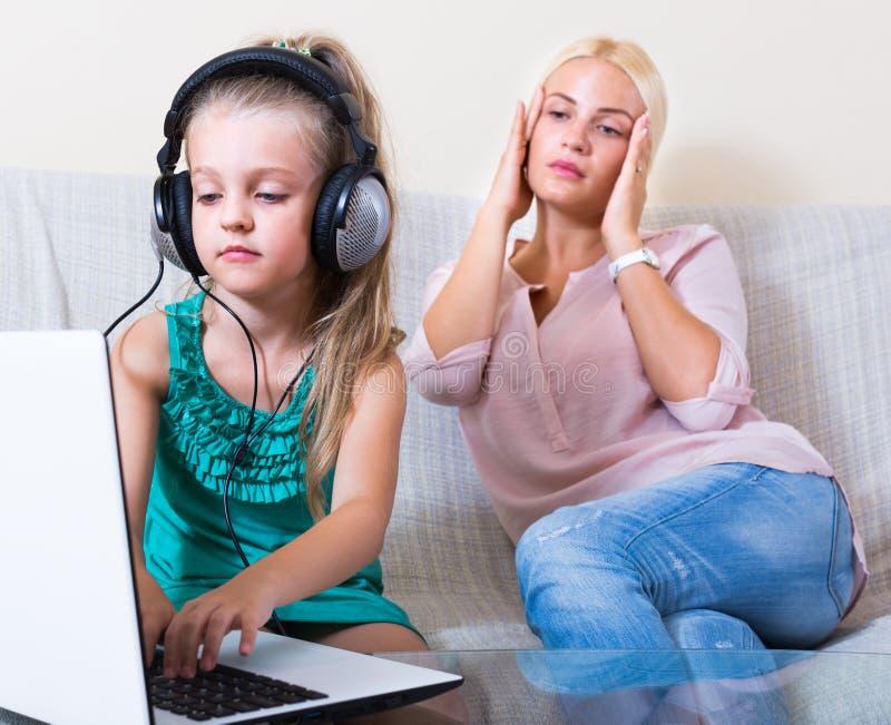 使用膝上型计算机的女儿而不是学习 免版税图库摄影