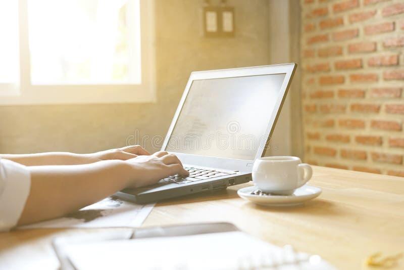 使用膝上型计算机的女商人为分析财政图表趋向预测计划在咖啡从窗口的咖啡馆阳光 免版税库存照片
