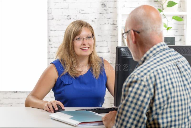 使用膝上型计算机的女商人和给劝告给她的客户 免版税库存图片