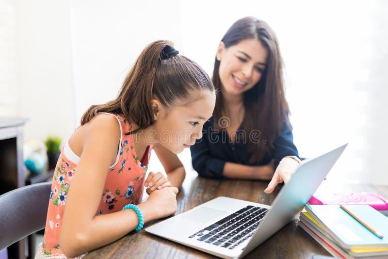 使用膝上型计算机的女孩和老师在表 免版税库存照片