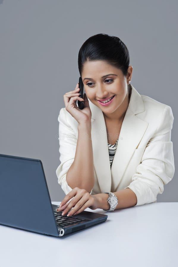 使用膝上型计算机的女实业家和谈话在一个手机 免版税库存图片