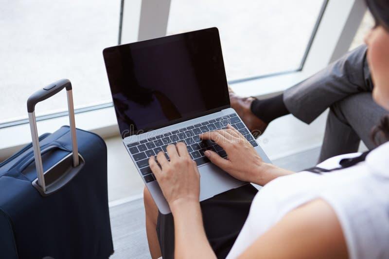 使用膝上型计算机的女实业家在机场离开休息室 免版税库存图片