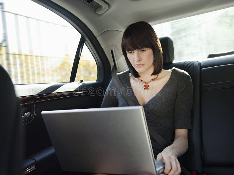 使用膝上型计算机的女实业家在汽车 免版税库存图片