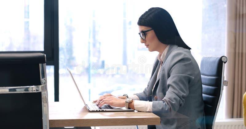 使用膝上型计算机的女实业家在起始的办公室 免版税图库摄影