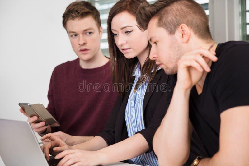 使用膝上型计算机的女实业家由同事 库存图片