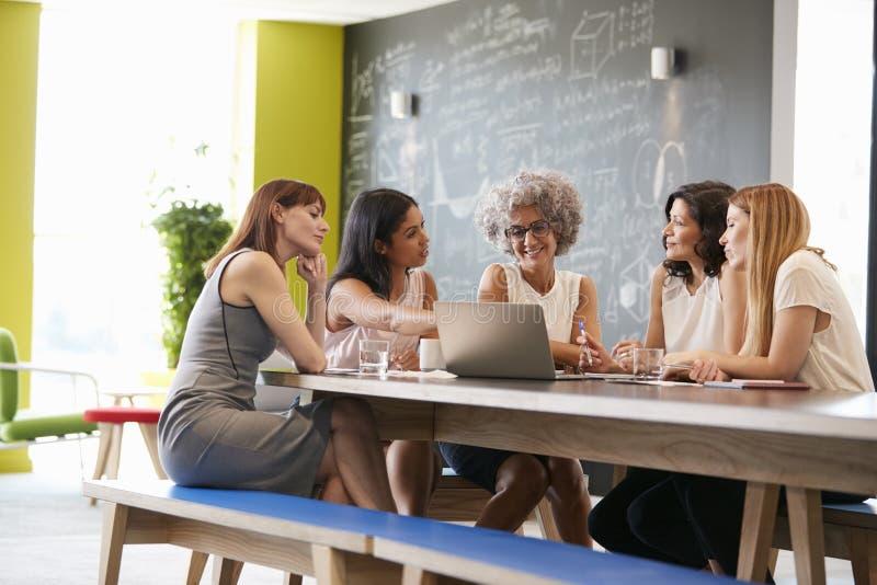 使用膝上型计算机的女性工作同事在一次非正式会议 免版税库存照片