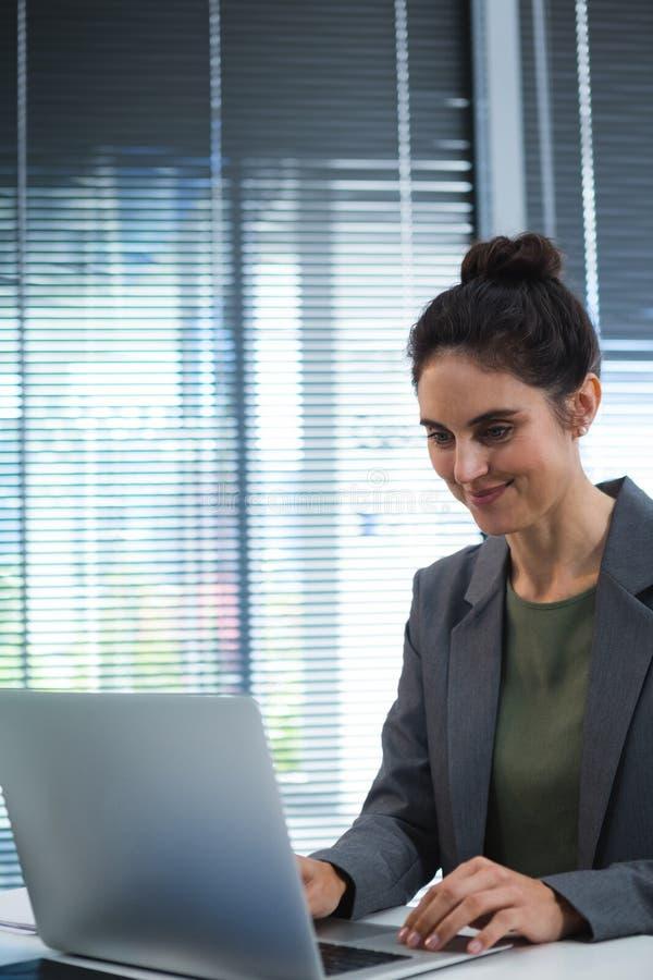 使用膝上型计算机的女性执行委员在书桌 库存照片