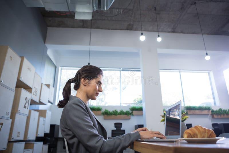 使用膝上型计算机的女性执行委员在书桌 免版税库存照片