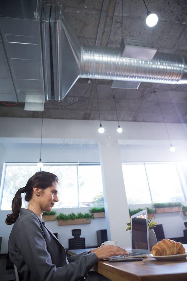 使用膝上型计算机的女性执行委员在书桌 免版税图库摄影