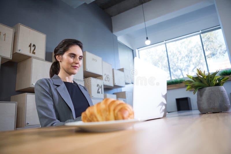 使用膝上型计算机的女性执行委员在书桌 免版税库存图片
