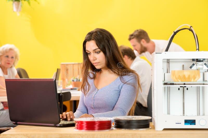 使用膝上型计算机的女性设计师由3D打印机在演播室 免版税库存照片