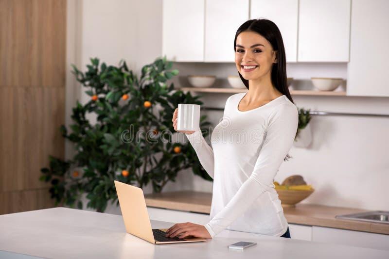 使用膝上型计算机的好微笑的妇女在厨房 免版税库存图片