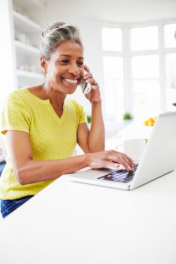 使用膝上型计算机的妇女和在家谈话在电话在厨房 库存照片