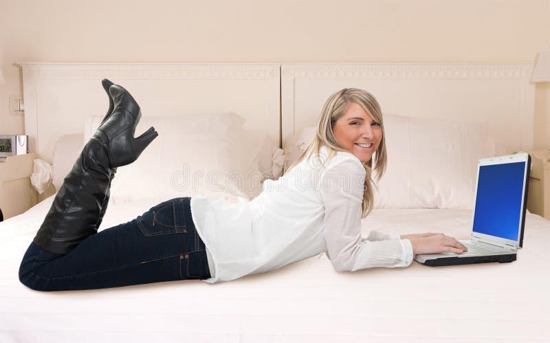 使用膝上型计算机的妇女在床 图库摄影