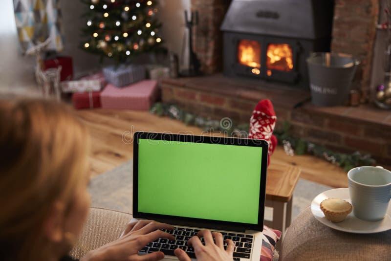 使用膝上型计算机的妇女在装饰的屋子里为圣诞节 免版税库存图片