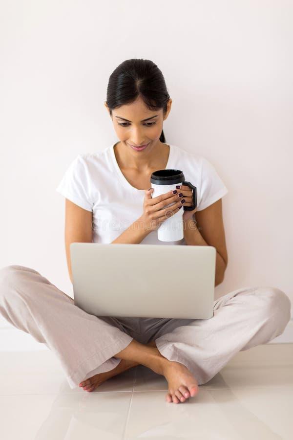 使用膝上型计算机的妇女地板 库存照片