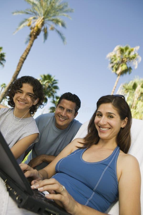 使用膝上型计算机的妇女户外与儿子(13-15)和丈夫低角度画象。 免版税图库摄影