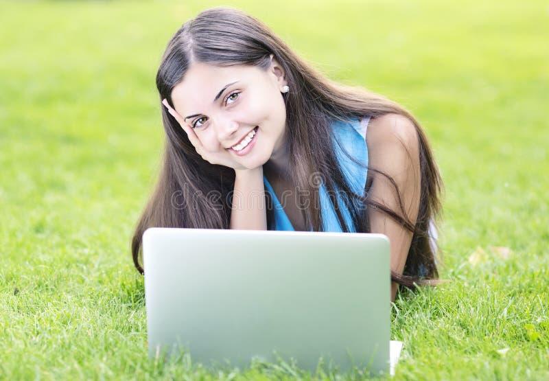 使用膝上型计算机的妇女户外 免版税库存图片