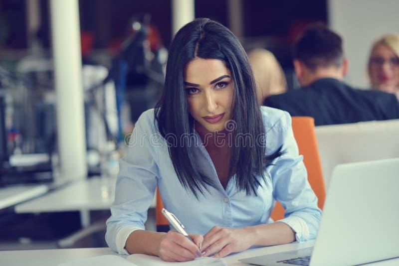 使用膝上型计算机的妇女的图象,当坐在她的书桌时 免版税图库摄影