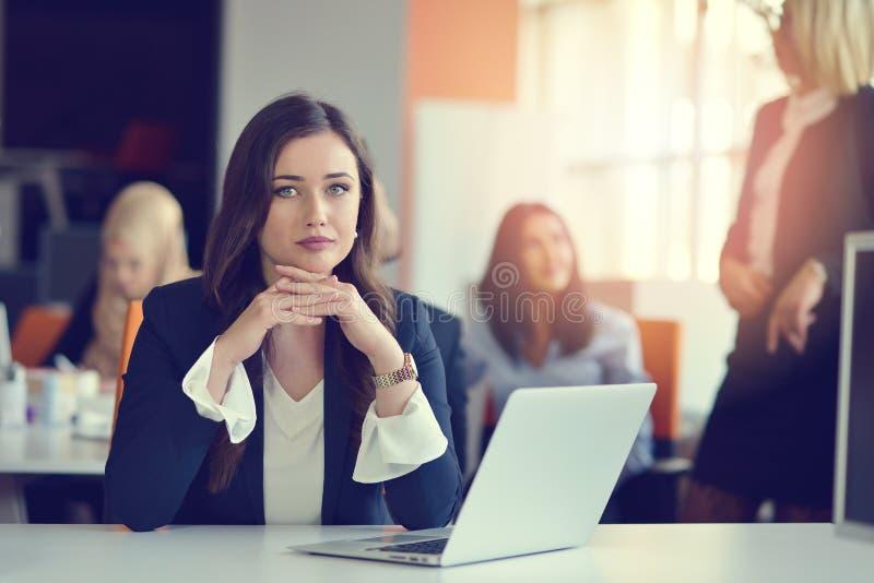 使用膝上型计算机的妇女的图象,当坐在她的书桌时 免版税库存照片
