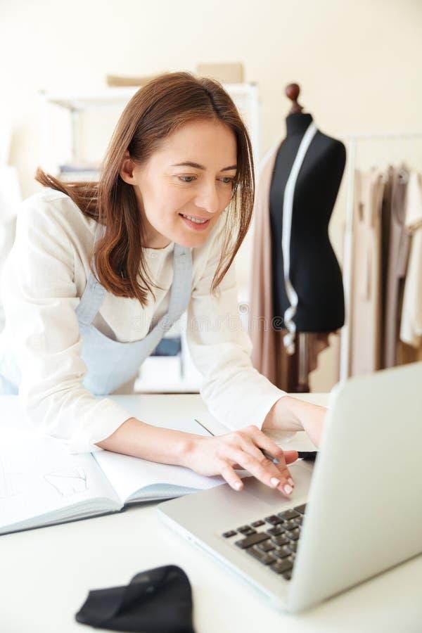 使用膝上型计算机的妇女裁缝为工作