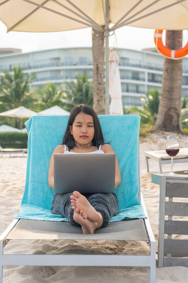 使用膝上型计算机的妇女,当放松在海滩时 库存图片