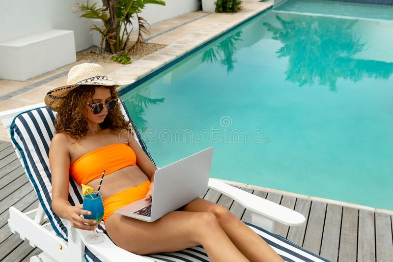 使用膝上型计算机的妇女,当有鸡尾酒饮料在后院在家时 免版税库存照片
