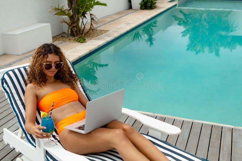 使用膝上型计算机的妇女,当有鸡尾酒饮料在后院在家时 免版税库存图片