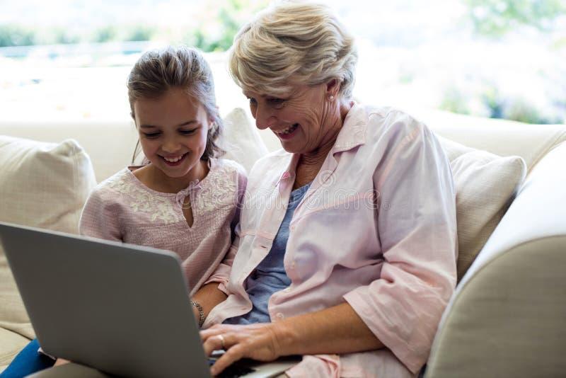 使用膝上型计算机的孙女和祖母 库存照片