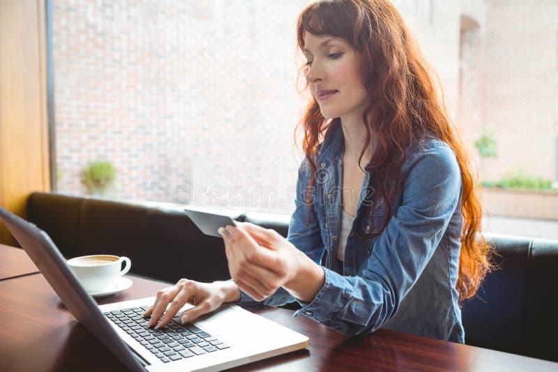 使用膝上型计算机的学生在咖啡馆在网上购物 免版税库存照片