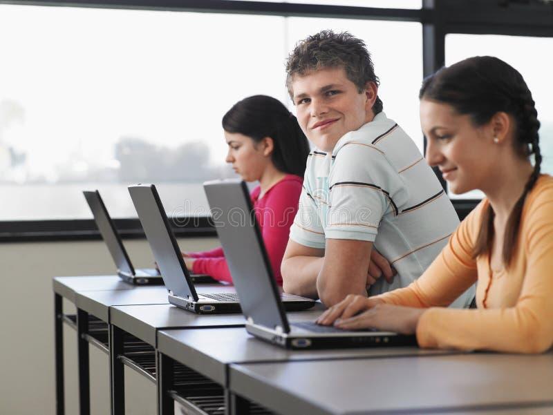 使用膝上型计算机的学生在计算机类 免版税图库摄影