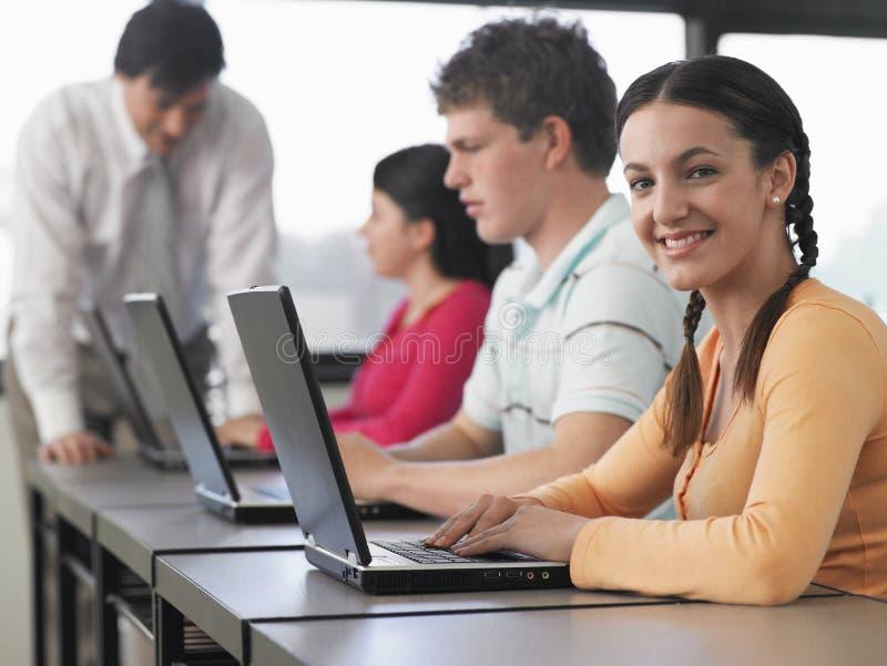 使用膝上型计算机的学生在计算机类 免版税库存照片