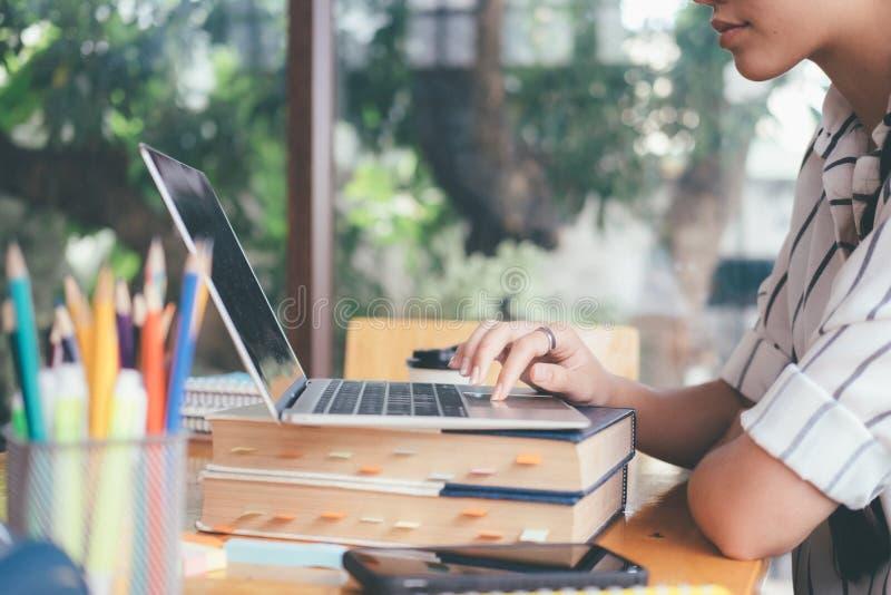 使用膝上型计算机的学院研究家庭作业的 免版税图库摄影