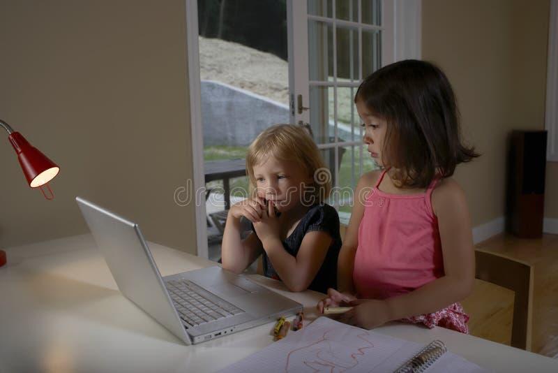 使用膝上型计算机的孩子在书房 免版税库存照片