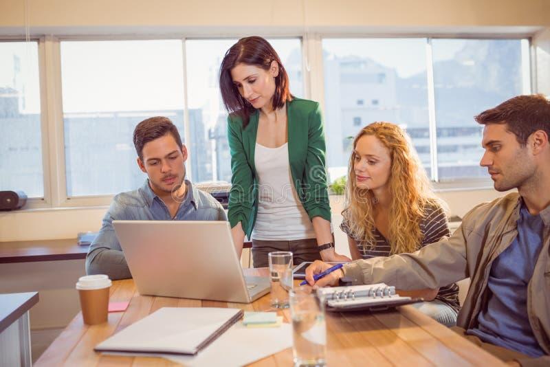 使用膝上型计算机的小组年轻同事 免版税图库摄影