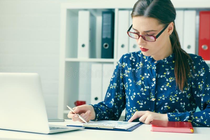 使用膝上型计算机的少妇和读年终报告文件在工作 企业服务台她的妇女工作 库存图片