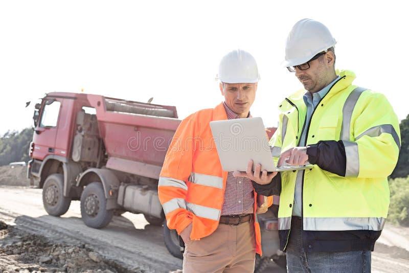 使用膝上型计算机的工程师在建造场所反对清楚的天空在晴天 免版税库存图片