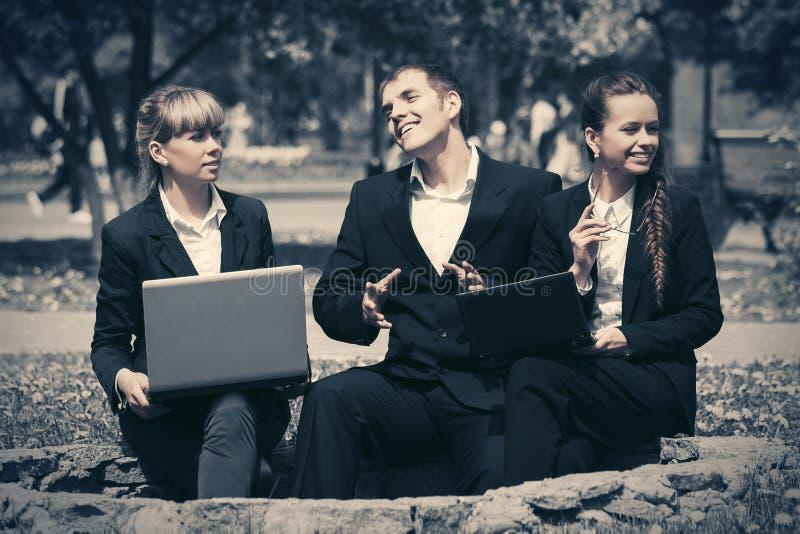使用膝上型计算机的年轻商人在城市公园 免版税库存照片